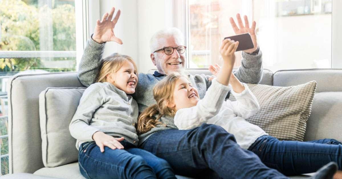 grandpére portant des les lunettes qui sourit pour le caméra de sa petite fille assis sur un canapé