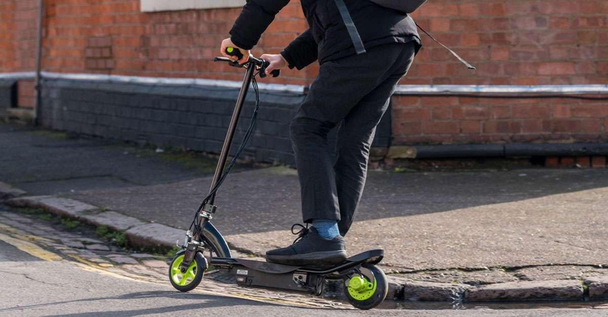 jeune homme à trottinette électrique en milieu urbain