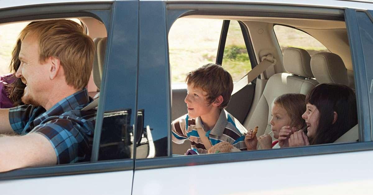 Famille au départ de vacances en voiture