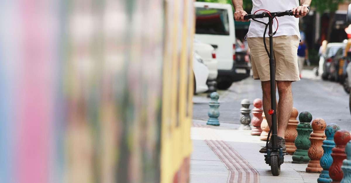 jeune homme à trottinette en ville sur le trottoir