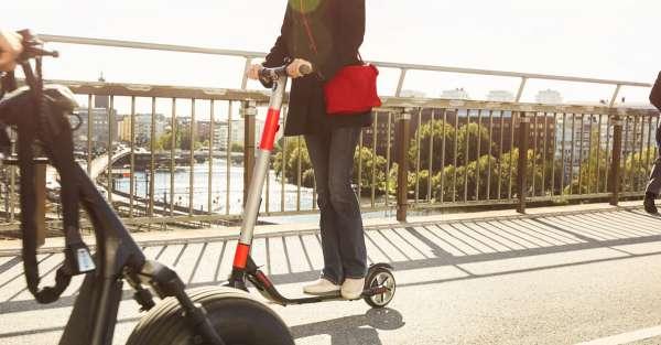Femme à trottinette électrique sur un pont à Paris portant un sac rouge