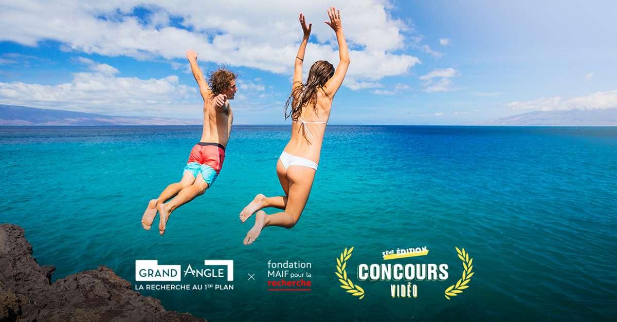 Deux jeunes personnes qui sautent d'une falaise dans l'océan