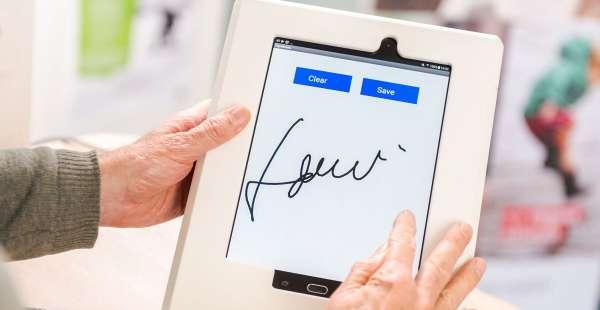 une personne signe sur une tablette