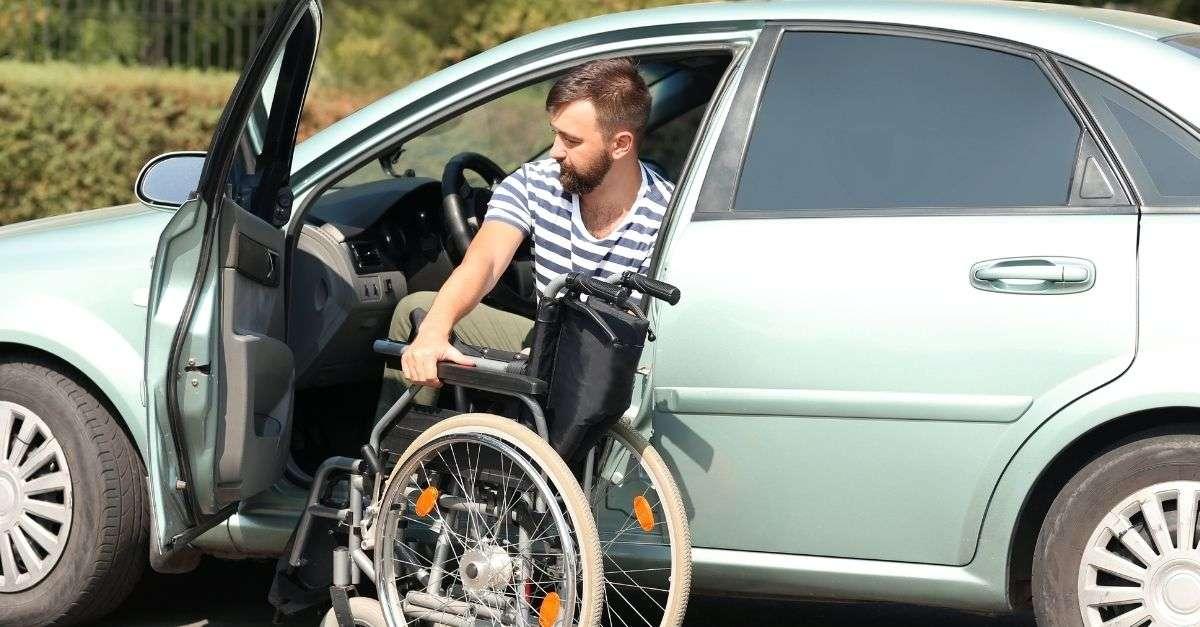 homme handicapé qui monte dans son véhicule en pliant sa chaise roulante
