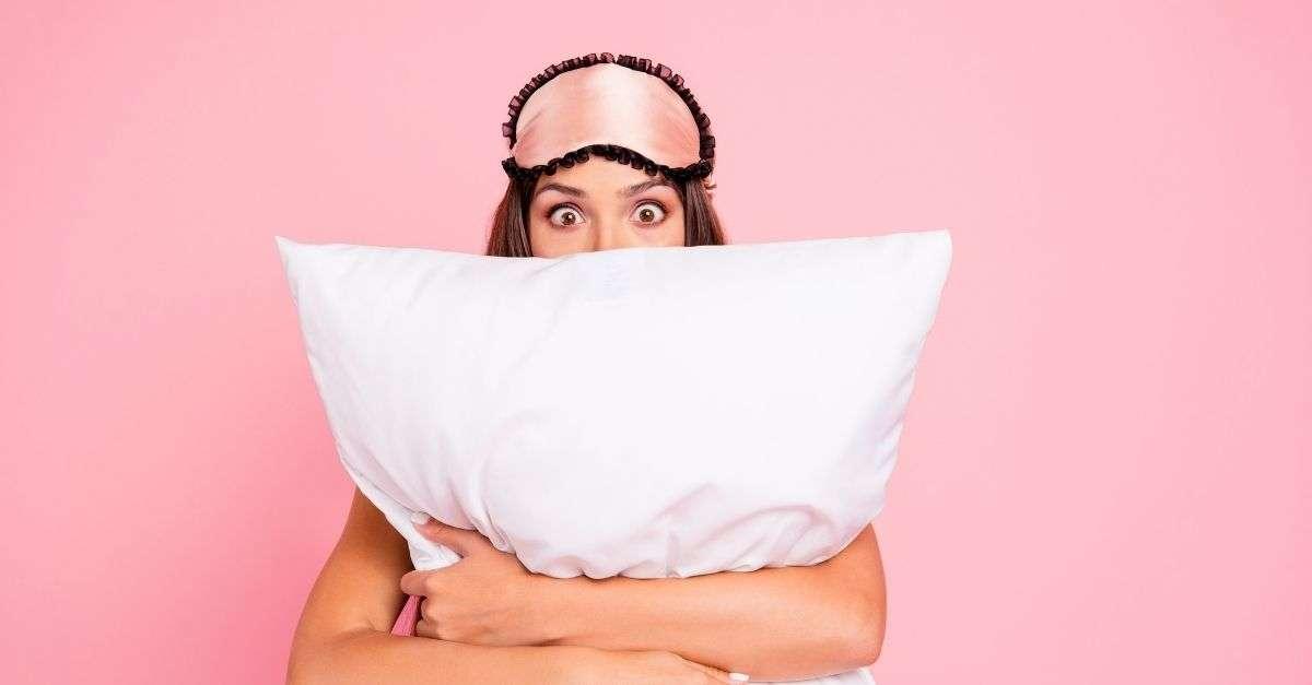 Femme insomniaque qui tient un oreiller dans ses bras