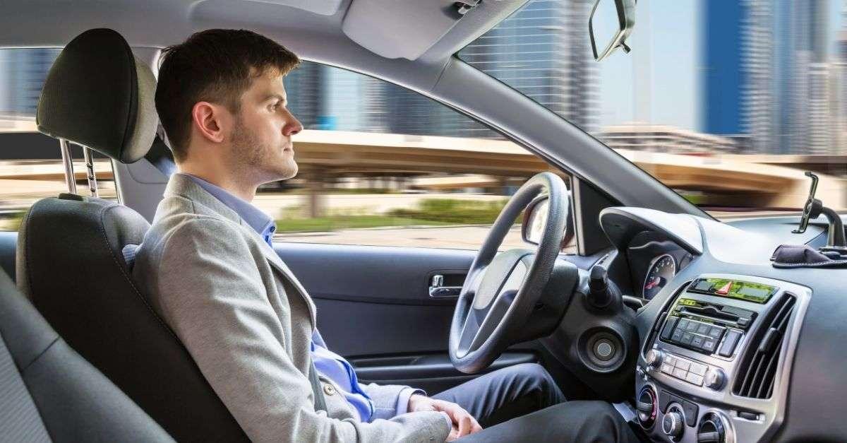 Homme dans une voiture atuonome sans les mains sur le volant mais attentif à la circulation