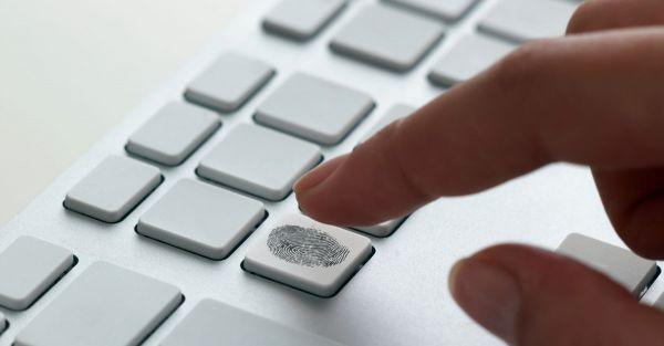 un doigt qui type sur un clavier blanc