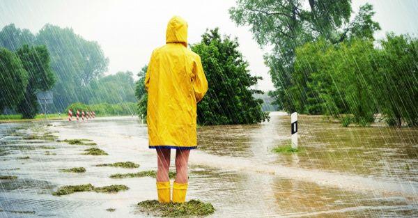 Une personne vue de dos habillée en ciré jaune lors d'une forte pluie et inondations