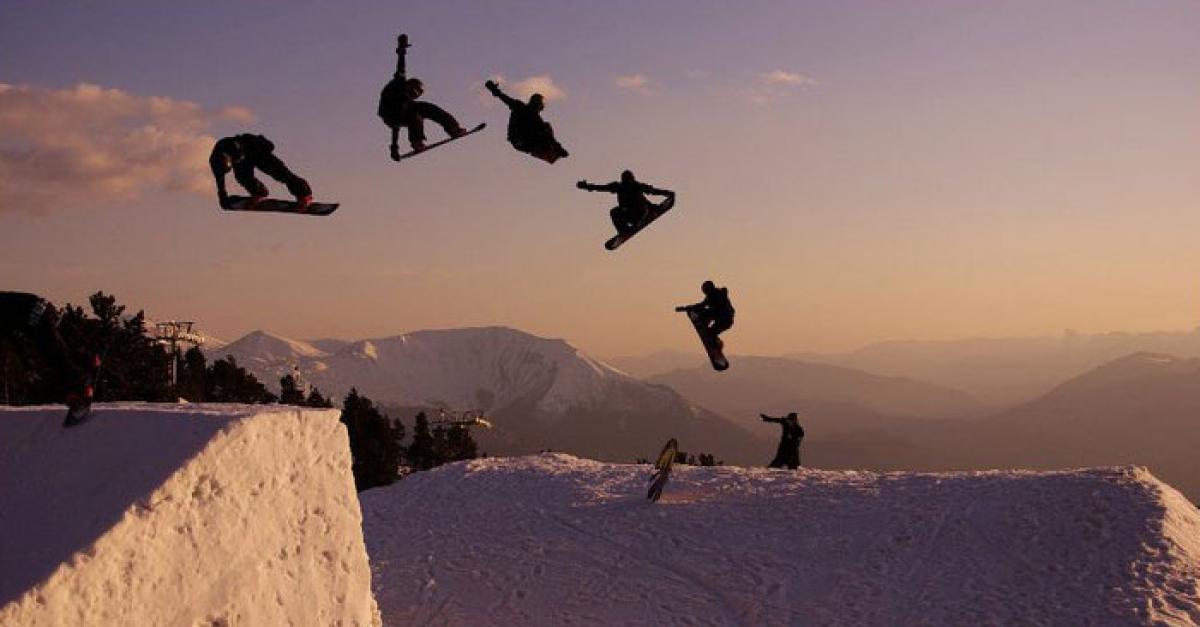 Snowboadrer qui fait un tour magnifique en snowpark