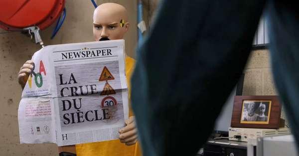 Didier le crash test dummy lit un journal avec la crue du siècle à la une